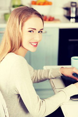 Beautiful woman sitting by the table with laptop