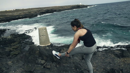 Young woman stretching leg on rocks by sea
