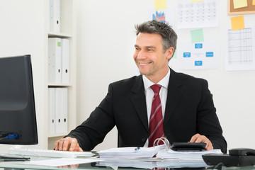 Smiling Businessman Working At Office Desk
