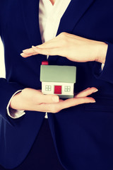 Close up on house model in business woman's hands.