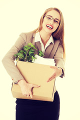 Business woman holding box with office items.