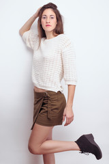 Young girl posing in studio with sweaters