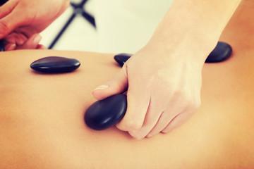 Female's back having stone massage.