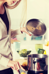 Beautiful caucasian woman is cooking.