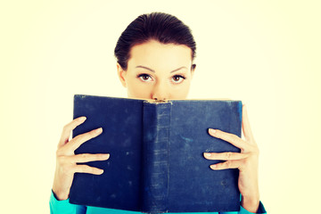 Student woman holding a book on her face.