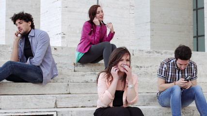 Four friends are talking on the phone sitting on the stairs - technology