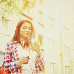 Teenage girl with smartphone and coffee outdoors