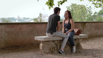 a young man and woman on a bench and talk and laugh - having a fun