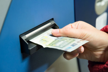 Woman Inserting Cash Into Machine
