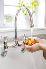 Washing tomatoes in kitchen sink
