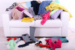 Messy colorful clothing on  sofa on light background - 76609173