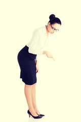 Business woman bending down and looking.