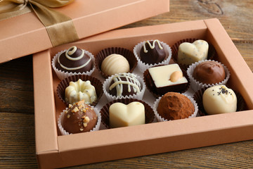 Delicious chocolate candies in gift box on table close-up