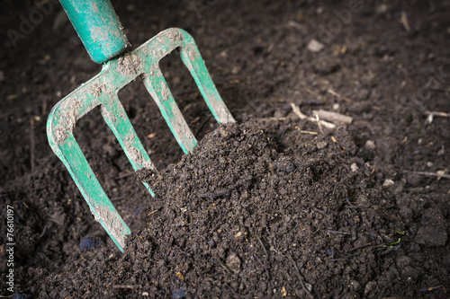Garden fork turning composted soil - 76610197