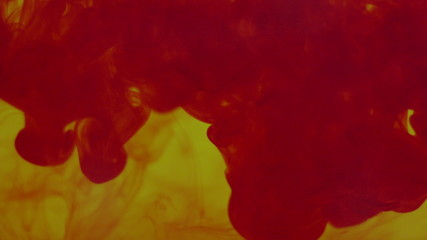 Abstract dynamic flow of red blood ink in water on dark yellow