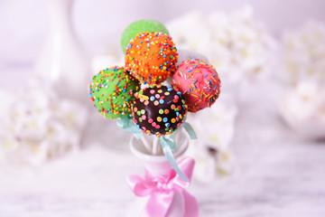 Sweet cake pops in vase on table on light background