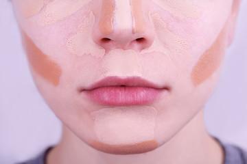 Applying makeup with cosmetic foundation, macro