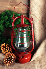 Kerosene lamp with wreath and cones on wooden planks background