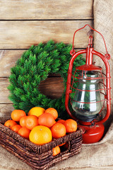Kerosene lamp with wreath and oranges in wicker basket