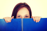 Woman behind blue workbook.