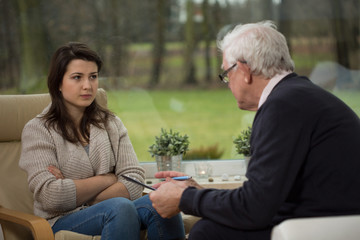 Girl talking with elder psychiatrist