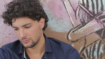 depressed and sad young man sitting near a graffiti wall