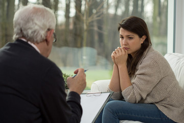 Sad teenager talking with psychologist