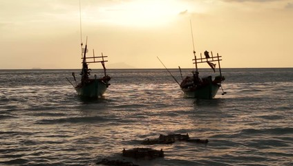 two fishing boats at sunset