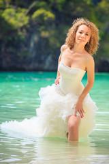 blonde bride stand in seawater