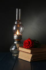 Kerosene lamp with books and red rose