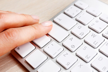 Female hand with keyboard on wooden desktop background
