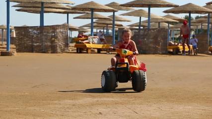 Little girl riding a toy car on the beach