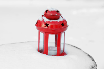 Decorative lantern on wooden stump over snow background