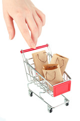 Female hand pushing small shopping cart with bags, isolated