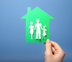 Cutout house with paper family in female hand