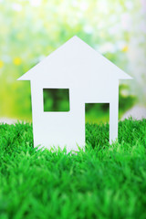 Cutout paper house on green grass and bright blurred background