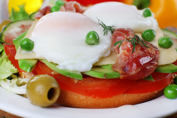 Sandwich with poached eggs, bacon and vegetables