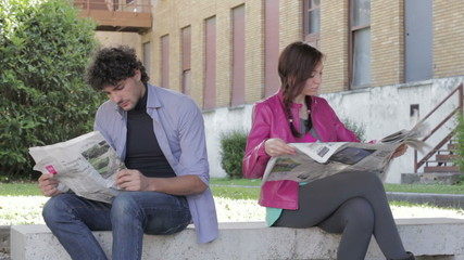a man and a woman are reading on newspaper