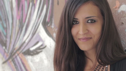 closeup of a beautiful woman smiling and laughing at the camera - graffiti
