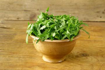 fresh green salad arugula in a wooden bowl