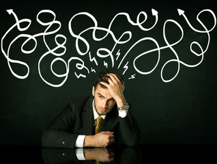 Depressed businessman sitting under drawn direction lines