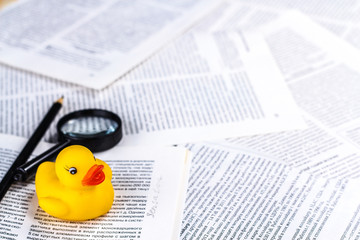 hoax symbol with rubber duck on newspaper