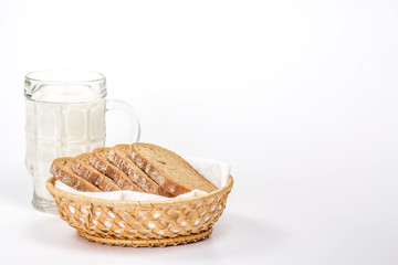 isolated basket of bread and glass of milk