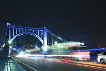 夜の清洲橋を走行する貨物トラック