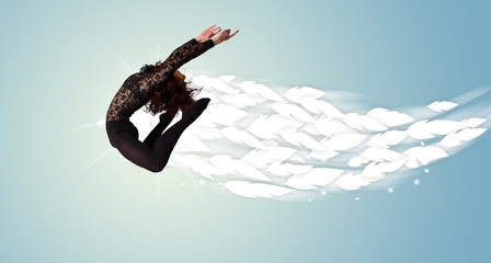 Healthy young woman jumping with feathers around her