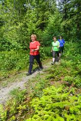 Drei Walkerinnen auf einem Waldtrail