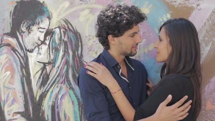 lover kissing in graffiti behind a couple kissing - love - hug