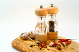 salt and pepper mill with ingredients around