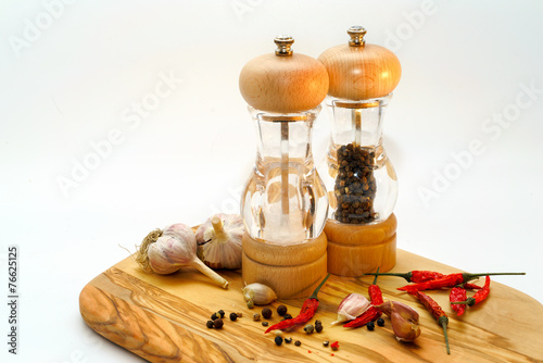 salt and pepper mill with ingredients around - 76625125