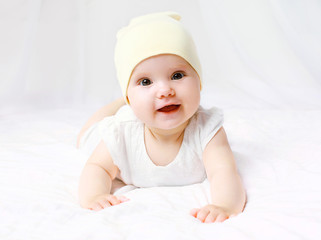 Cute baby in hat on the bed at home